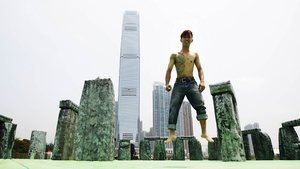 A man bounces on 'Sacrilege 2012', a life-size inflatable sculpture of Stonehenge by English contemporary artist Jeremy Deller, part of the Inflation exhibition in Hong Kong
