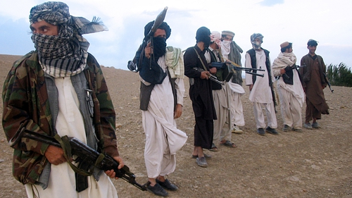 This file photo shows fighters with Afghanistan's Taliban militia standing on a hillside at Maydan Shahr in Wardak province, west of Kabul