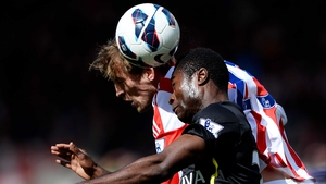 Alexander Tetley of Norwich and Peter Crouch of Stoke compete for a header