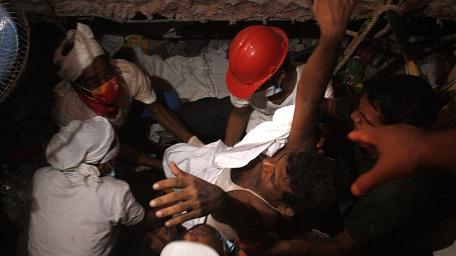 Bangladeshi rescuers carry a survivor who was recovered yesterday