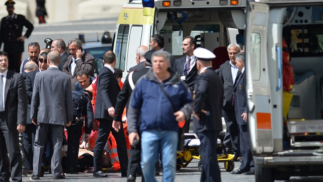 A policeman is helped after being shot in Rome, outside the palazzo Chigi, the Italian prime minister's offices