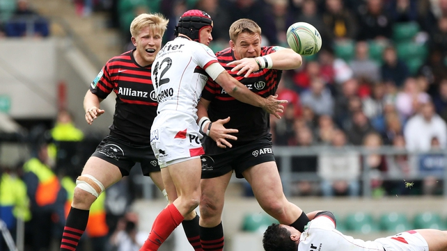 John Smit of Saracens loses the ball as he is tackled by Matt Giteau (left) and Chris Masoe (right)