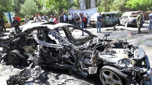 People gather at the scene of the explosion in the Mezze district of Damascus