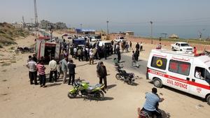 Palestinians gather around the scene following the Israeli raid