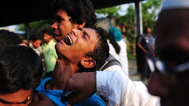 A Bangladeshi youth reacts after seeing his relatives dead body following the building collapse