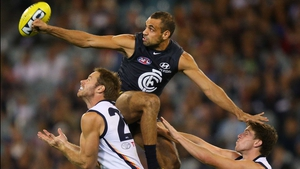Chris Yarran of the Blues punches the ball away against the Crows during the AFL match at the MCG in Melbourne
