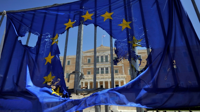 A burned EU flag hangs on the barriers protecting the Greek parliament