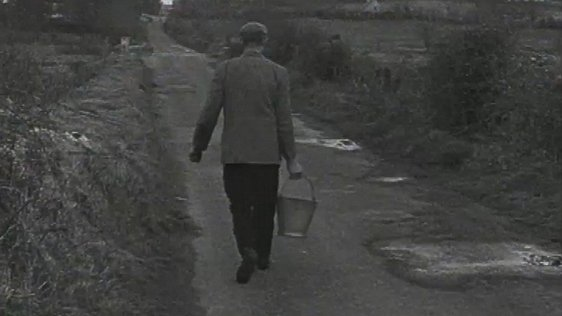 A farmer carries a bucket of water along a country road.