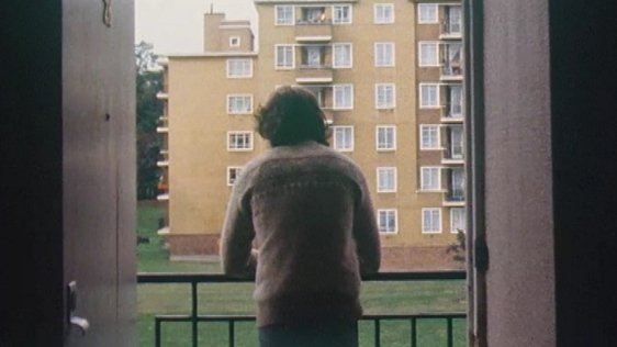 A young Irish man on the balcony of a Brixton flat. An image from a report on Irish emigration to London.