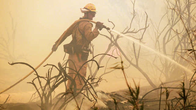 A firefighter sprays water on a flare up as a wildfire burns along the Pacific Coast Highway