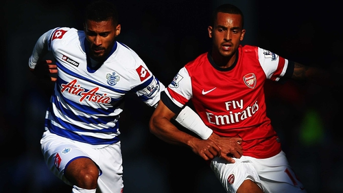 Armand Traore (L) of Queens Park Rangers holds off the challenge of Theo Walcott