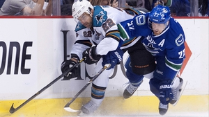 Daniel Sedin of the Vancouver Canucks and Dan Boyle of the San Jose Sharks clash during the NHL Stanley Cup play offs