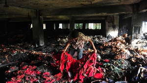 A Bangladeshi garment worker holds up burnt cloth inside the gutted factory in Dhaka