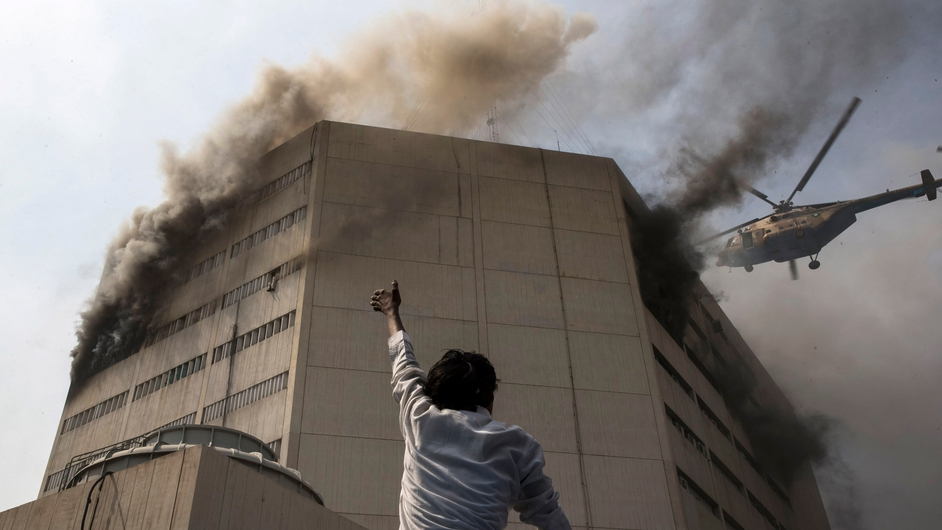 A by-stander points to a man trapped by a fire in the Lahore Development Authority Plaza in Pakistan