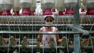 An employee operates machines for making yarn at a textile factory in Jiujiang, China