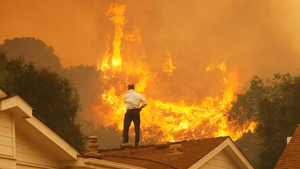 A man looks at the approaching flames of wildfires near Camarillo in California