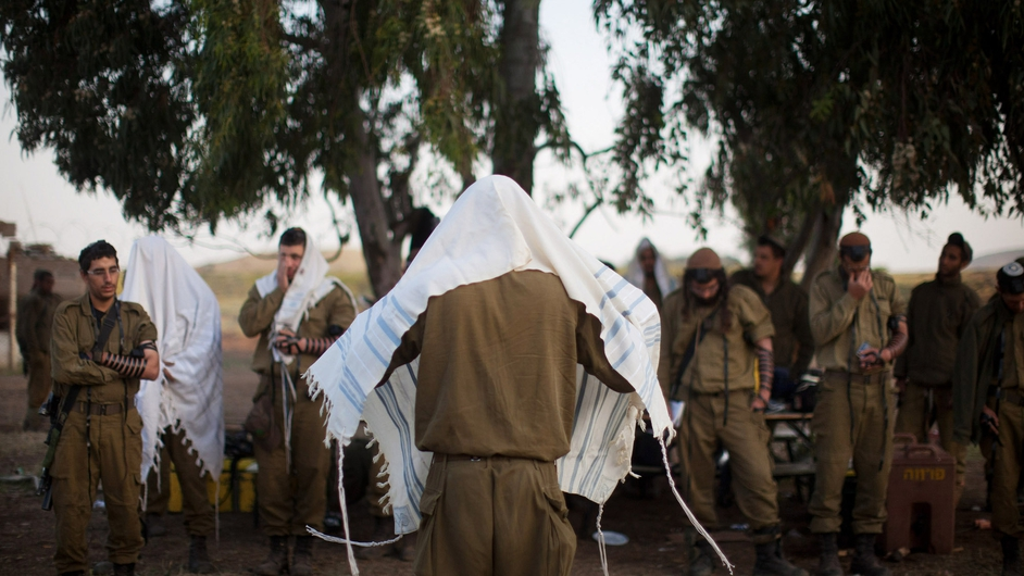 Israeli soldiers of the Golani brigade pray while taking part in a military exercise near the border with Syria
