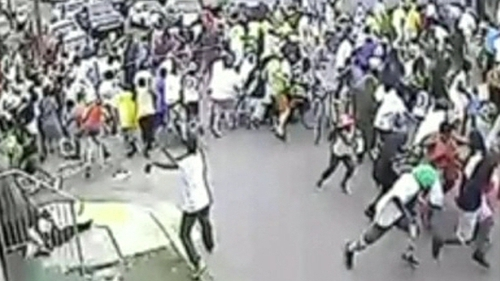 The footage shows a crowd scattering