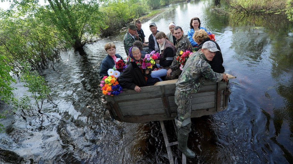 People hitch a ride across a flooded area near the Belarus village of Khlupin, to visit the graves of relatives and friends