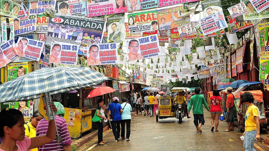 Voters walk beneath election posters, suspended over a street in a polling precinct in the Philippine capital Manila