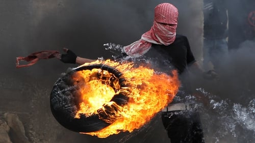 A Palestinian sets fire to a tyre during clashes between hundreds of Palestinians and Israeli soldiers