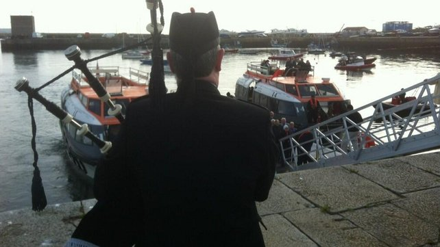 Piper greets QM2 passengers arriving by tender at Dún Laoghaire