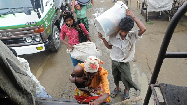 Rohingya family members carry their belongings as they prepare to move to safer ground