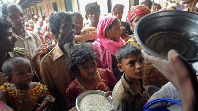 A group of Rohingya families wait for rice as the cyclone sent heavy rain and strong winds