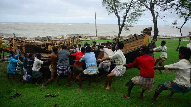 Bangladeshis shift a boat away from the beachfront as the cyclone heads towards landfall