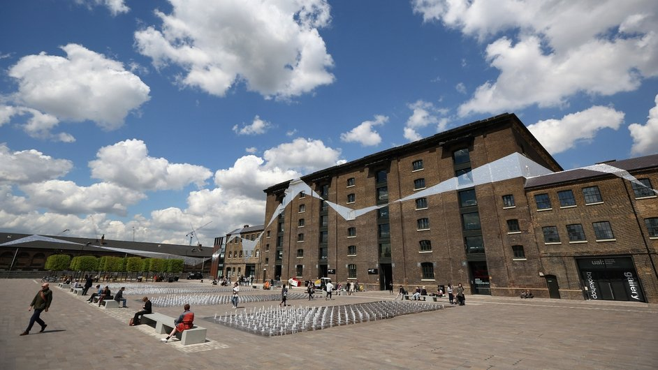 Members of the public relax in front of a section of the artwork Across the Buildings by Swiss artist Felice Varini in Granary Square in London's King's Cross