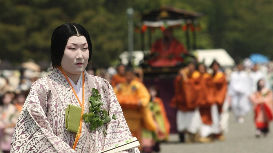 A Japanese woman dressed in traditional costume walks in the procession of the Aoi Festival at the Imperial Palace in Kyoto