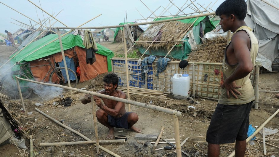 A man constructs a tent in a camp in the village of Mansi for people displaced by a cyclone in Bangladesh
