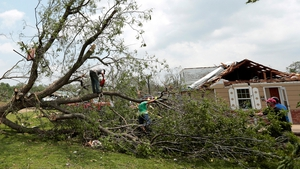 Volunteers chain saw a fallen tree knocked down by a tornado near Shawnee