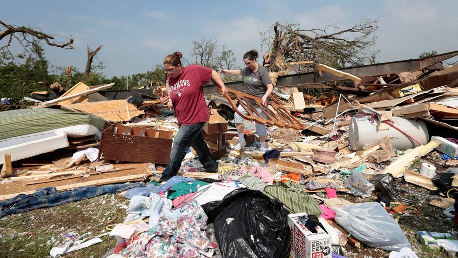 Candice Lopez (L) and Stephanie Davis help clean debris from Thelma Cox's mobile home after it was destroyed by a tornado near Shawnee