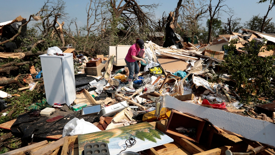 Kasey Clark sorts through debris in her grandmother-in-law's destroyed home