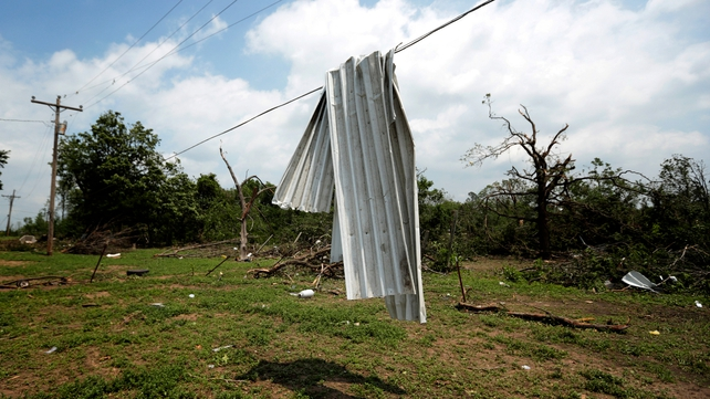 A sheet of corrugated tin lies across a power line near Shawnee