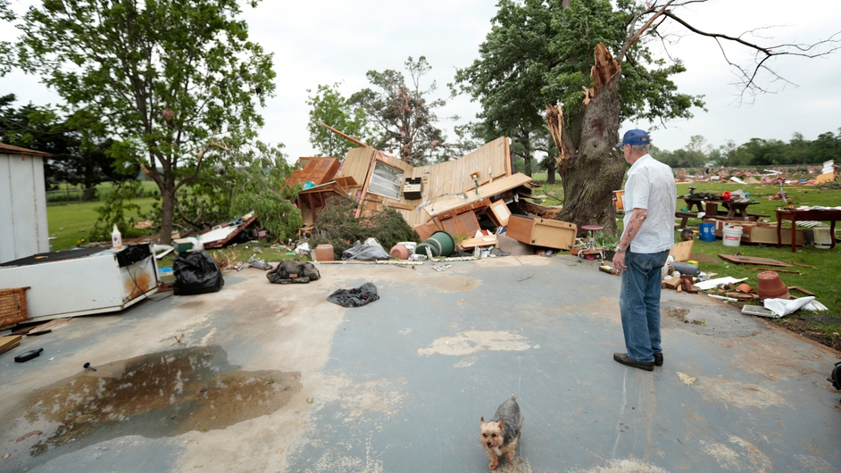 Lonnie Langston stands near his garage, which was swept off the concrete pad next to his house by a tornado