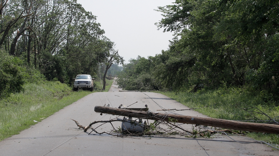An electrical pole and trees lie across a country road in Oklahoma