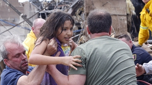 A child is pulled from the rubble of the Plaza Towers Elementary School  in Moore