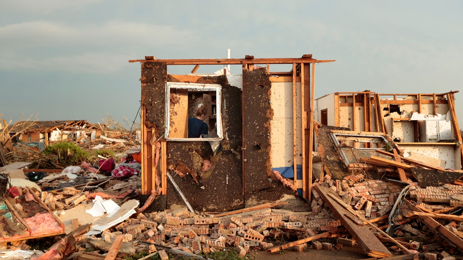 Dana Ulepich searches inside a room left standing at the back of her house in Moore