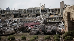 Flipped vehicles are piled up outside the heavily damaged Moore Medical Center