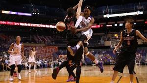 Alexis Hornbuckle of the Phoenix Mercury passes the ball around Arisa Fujiwara during the preseason WNBA game in Phoenix