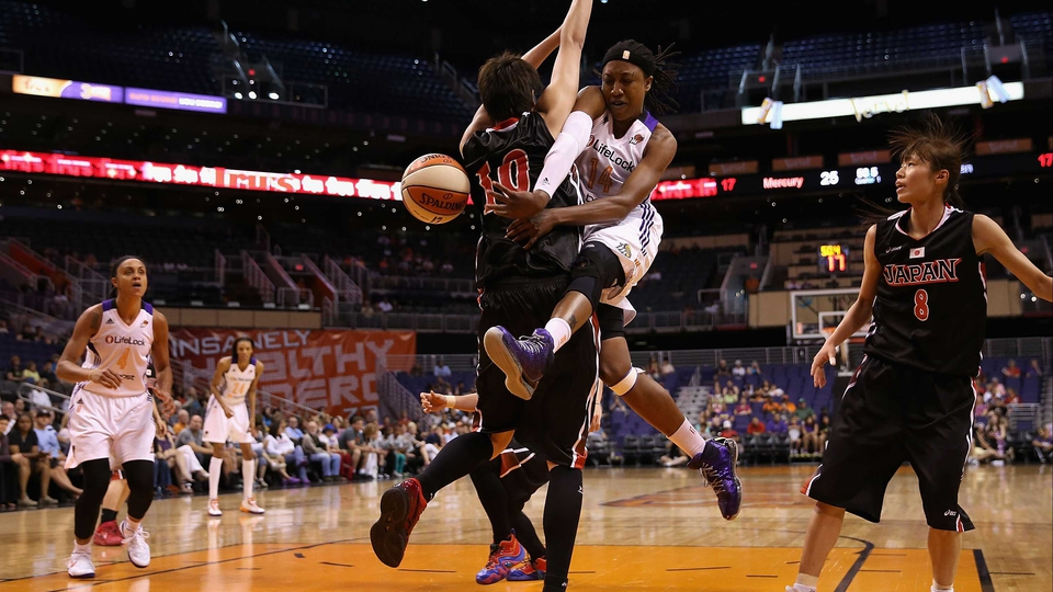 Alexis Hornbuckle of the Phoenix Mercury passes the ball around Arisa Fujiwara during the preseason WNBA game in Phoenix