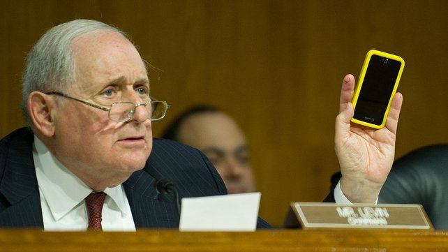 Chairman of the Permanent Subcommittee on Investigations US Senator Carl Levin holds up his Apple iPhone as he questions Apple CEO Tim Cook