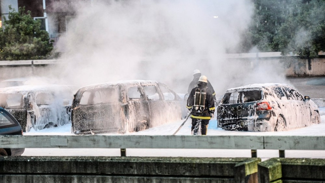 Policemen extinguish burning cars after youths rioted in Husby, northern Stockholm