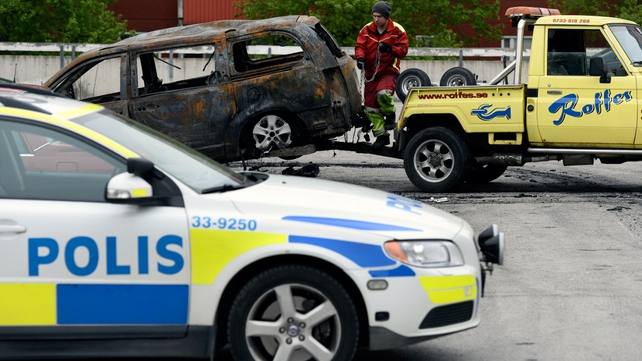 A burnt-out van is prepared for removal following riots in Husby