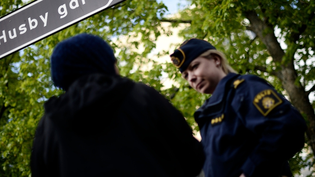 A policewoman speaks with a resident of Husby during a demonstration against police violence and vandalism