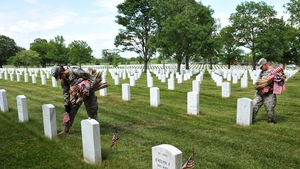 Staff Sergeant Joelle Monroe (L) of the Third US Infantry Regiment, The Old Guard, places flags in front of graves at Arlington National Cemetery ahead of Memorial Day