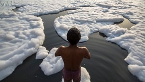 An Indian bathes in an industrial waste-foam polluted section of the Yamuna River