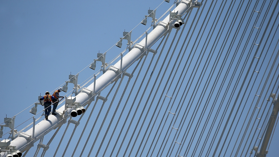 Workers walk on a cable of the newly constructed eastern span of the San Francisco-Oakland Bay Bridge